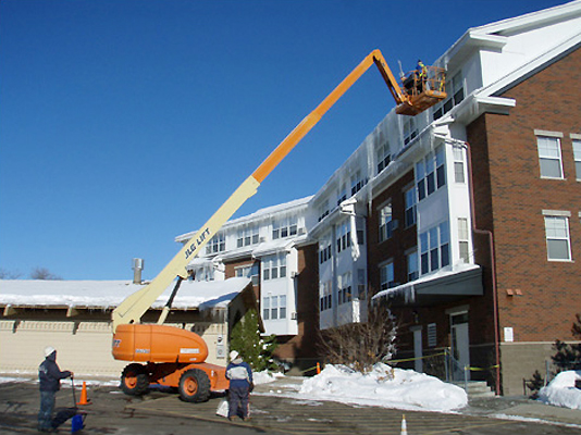 Xtreme Exteriors crew expertly removing ice buildup on multi-story apartment building using cherry picker crane