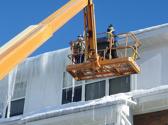 Xtreme Exteriors crew expertly removing ice buildup on multi-story apartment building